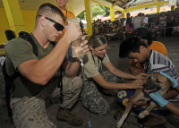 "Goutteur utilisé pour réhydrater un chien. (fichier Wikimedia Commons : ""Learning_How_to_drip_to_a_dehydrated_dog_during_a_veterinary_civic_action_project"") (domaine public) U.S. Department of Defense, 2012"
